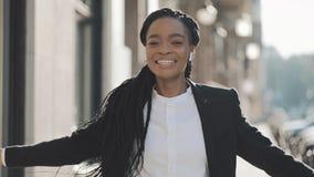 Młody szczęśliwy amerykanin afrykańskiego pochodzenia bizneswoman chodzi miasto ulicę w słuchawkach podczas gdy słuchający muzyka zbiory