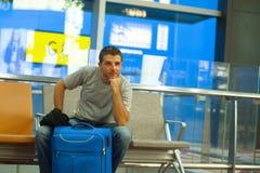 Młody szczęśliwy, atrakcyjny turystyczny mężczyzna obsiadanie z walizką przy lotniskowym wyjściowym abordaż bramy czekaniem i zdjęcie stock