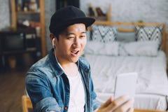Młody szczęśliwy Azjatycki mężczyzna opowiada wideo wezwanie przez smartphone jest ubranym hełmofony w domu zdjęcie stock