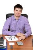 Młody szczęśliwy biznesmen pracuje na jego biurku zdjęcia royalty free