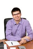 Młody szczęśliwy biznesmen pracuje przy jego biurkiem fotografia royalty free
