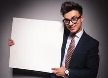 Młody szczęśliwy biznesmen przedstawia pustą deskę Obrazy Stock