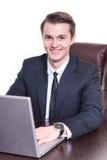 Młody szczęśliwy biznesmena obsiadanie w działaniu na laptopu ono uśmiecha się i biurze fotografia stock