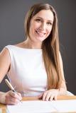 Młody szczęśliwy bizneswoman podpisuje kontrakt w biurze Obrazy Stock