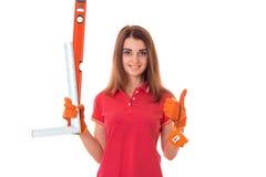 Młody szczęśliwy brunetki kobiety budowniczy w mundurze z narzędziami w jej rękach robi reovations odizolowywającym na białym tle Zdjęcia Royalty Free