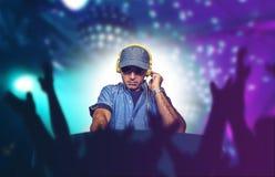 Młody szczęśliwy, chłodno DJ bawić się muzykę przy partyjnym wydarzeniem w noc klubie miesza techno piosenki na światła  obraz stock