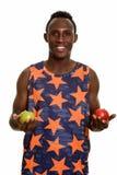 Młody szczęśliwy czarnego afrykanina mężczyzna ono uśmiecha się podczas gdy trzymający zielony i ponowny Zdjęcie Stock