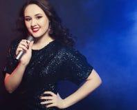 Młody szczęśliwy dziewczyna śpiew w mikrofon przy przyjęciem Obraz Stock