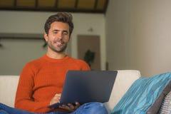 Młody szczęśliwy i atrakcyjny mężczyzna pracować relaksował z laptopem przy nowożytnego mieszkania żywym izbowym obsiadaniem przy obrazy royalty free