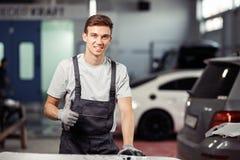 Młody szczęśliwy i uśmiechnięty mechanik stoi blisko samochodów przy samochód usługą zdjęcia royalty free