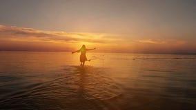 Młody szczęśliwy kobieta bieg na plaży kamera z powrotem zbiory