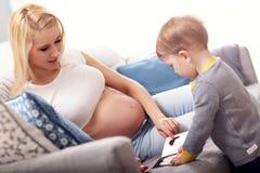 Młody Szczęśliwy kobieta w ciąży bawić się z synem zdjęcia royalty free