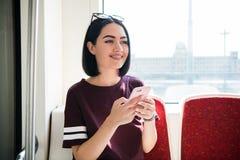 Młody szczęśliwy kobiety obsiadanie w miasto autobusie i używać jej telefon komórkowego fotografia stock