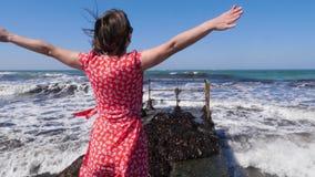 Młody szczęśliwy kobiety odprowadzenie na molu w kierunku burzowego morza z falami rozprzestrzenia ona ręk w oddaleniu pozować Si zbiory wideo
