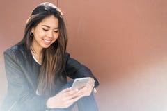Młody szczęśliwy kobiety talikng i texting wiadomość z jej wiszącą ozdobą ph obrazy royalty free