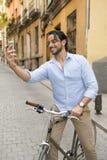 Młody szczęśliwy mężczyzna bierze selfie z telefonem komórkowym na retro chłodno rocznika rowerze Fotografia Stock