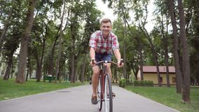 Młody szczęśliwy mężczyzna jedzie rocznika bicykl przy parkową drogą i słuchającą muzyką Sporty faceta kolarstwo plenerowy i śpie zdjęcie wideo