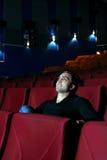 Młody szczęśliwy mężczyzna ogląda film i odpoczywa w kinowym teatrze fotografia stock
