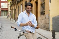 Młody szczęśliwy mężczyzna ono uśmiecha się używać telefon komórkowego na rocznika chłodno retro rowerze obrazy royalty free