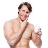 Młody szczęśliwy mężczyzna stosuje płukankę na twarzy Zdjęcia Stock
