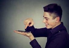 Młody szczęśliwy mężczyzna używa smartphone zdjęcia royalty free