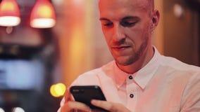 Młody szczęśliwy mężczyzna używa smartphone przy wygodną kawiarnią przy wieczór czasem Komunikacja, biznes, podróż, datuje pojęci zbiory wideo