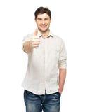 Młody szczęśliwy mężczyzna z aprobatami podpisuje wewnątrz przypadkowego Zdjęcia Stock