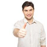 Młody szczęśliwy mężczyzna z aprobatami podpisuje wewnątrz przypadkowego Obrazy Stock
