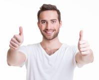 Młody szczęśliwy mężczyzna z aprobatami podpisuje wewnątrz przypadkowego. Obraz Royalty Free