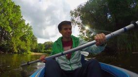 Młody szczęśliwy męski paddling kajak, krańcowi sporty, gopro, emocje zbiory