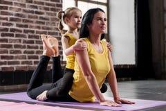 Młody szczęśliwy macierzysty robi rozciągania ćwiczenie na macie podczas gdy jej uśmiechnięta córka ściska ona w klubie sportowym Fotografia Stock