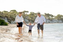Młody szczęśliwy matki i ojca odprowadzenie na plaży w rodzinnego wakacje pojęciu Zdjęcia Royalty Free