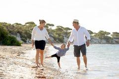 Młody szczęśliwy matki i ojca odprowadzenie na plaży w rodzinnego wakacje pojęciu Obraz Stock