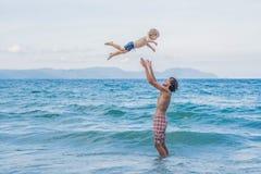 Młody szczęśliwy ojciec trzyma up w jego ręka małym synu stawia on obrazy stock