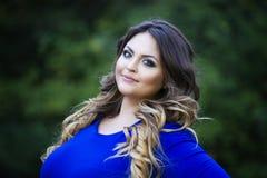 Młody szczęśliwy ono uśmiecha się plus rozmiaru model w błękit sukni, xxl kobiecie na naturze, fachowym makeup i fryzurze outdoor obrazy royalty free