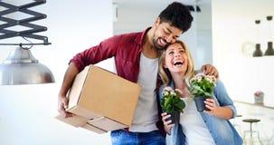 Młody szczęśliwy pary chodzenie w nowych domu i odpakowania pudełkach zdjęcia stock