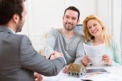 Młody szczęśliwy pary handshaking agent nieruchomości po podpisywać c Fotografia Stock