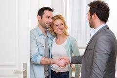 Młody szczęśliwy pary handshaking agent nieruchomości po podpisywać c Obrazy Stock