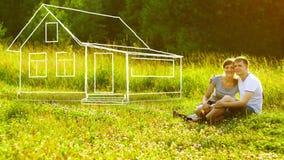 Młody szczęśliwy pary obsiadanie na zielonej trawie w parkowym i marzyć wokoło je swój dom 100 rachunków pojęcia dolara dom robić ilustracji