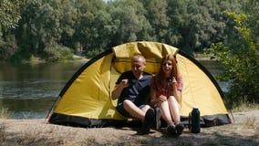 Młody szczęśliwy pary obsiadanie w namiocie ogląda widok Pić herbaty, śmiechu i rozmowy, Las i rzeka na tle zbiory wideo