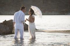 Młody szczęśliwy pary odprowadzenie wzdłuż plaży kołysa przy wschodem słońca Zdjęcia Stock