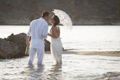 Młody szczęśliwy pary odprowadzenie wzdłuż plaży kołysa przy wschodem słońca Fotografia Stock