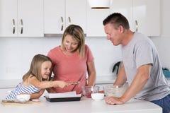 Młody szczęśliwy pary pieczenie wraz z małą młodą piękną córki kuchnią ma zabawę bawić się z śmietanką w rodzinnym li w domu Fotografia Royalty Free