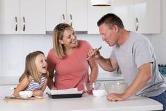 Młody szczęśliwy pary pieczenie wraz z małą młodą piękną córki kuchnią ma zabawę bawić się z śmietanką w rodzinnym li w domu Obrazy Royalty Free