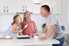 Młody szczęśliwy pary pieczenie wraz z małą młodą piękną córki kuchnią ma zabawę bawić się z śmietanką w rodzinnym li w domu Obraz Stock