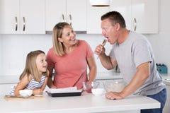 Młody szczęśliwy pary pieczenie wraz z małą młodą piękną córki kuchnią ma zabawę bawić się z śmietanką w rodzinnym li w domu Obrazy Stock
