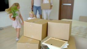 Młody szczęśliwy rodzinny chodzenie nowy mieszkanie Dwa małej dziewczynki biega w nowego dom z rodzicami przy tło kartonem zdjęcie wideo