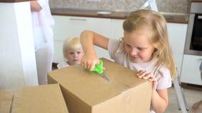 Młody szczęśliwy rodzinny chodzenie nowy mieszkanie Dwa małej dziewczynki biega w nowego dom z rodzicami przy tło kartonem zbiory wideo