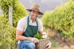 Młody szczęśliwy rolnik trzyma kosz warzywa zdjęcia royalty free
