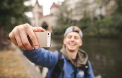 Młody szczęśliwy turysta bierze selfie przeciw tłu historyczni budynki, ono uśmiecha się i jezioro i obrazy royalty free